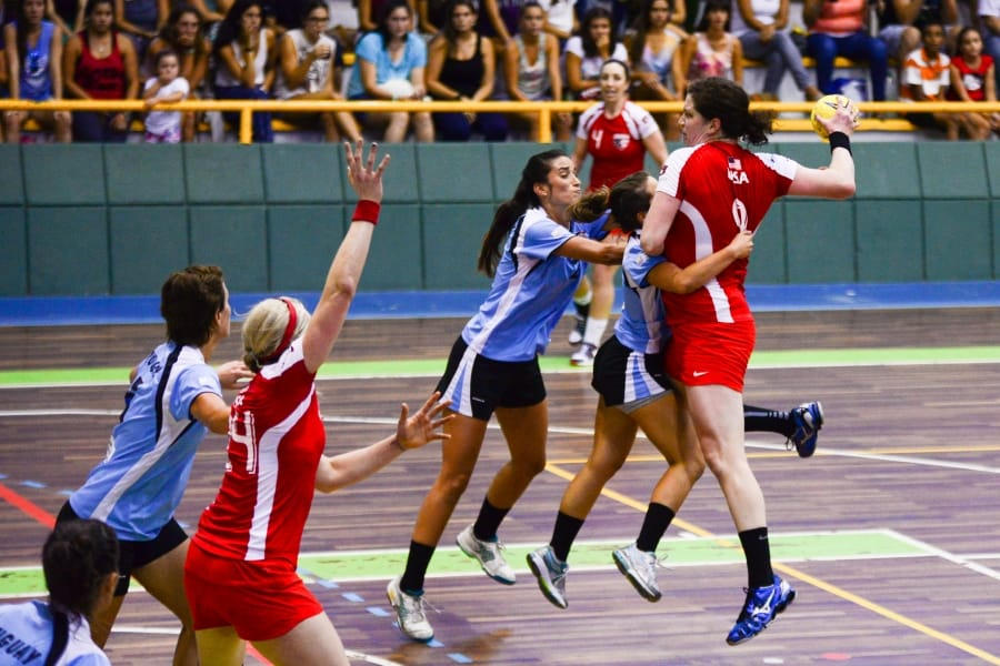 An action shot of Kathy Darling taking a jumpshot against Uruguay in a team handball match.
